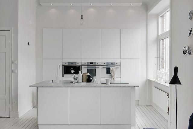 Une cuisine blanche minimaliste épurée encastrée ilot central table de cuisson aspirante