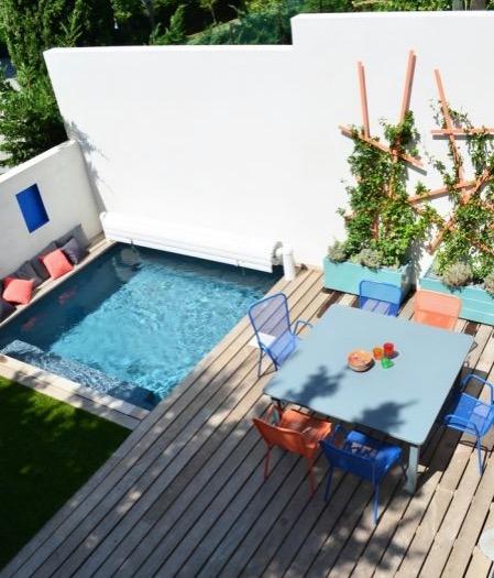 Petite piscine carrée et terrasse colorée.