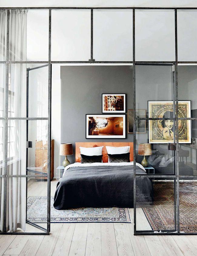 dans un loft, les espaces sont séparés avec de grandes verrières d'atelier et la couleur est amenée par un tapis persan