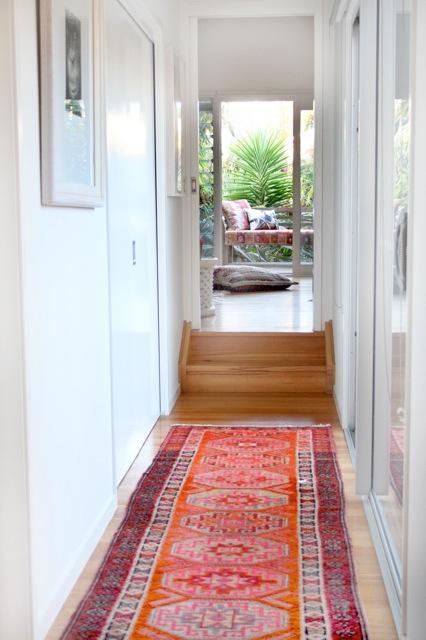 ambiance cosy et chaleureuse dans le couloir grâce à un tapis coloré persan rouge