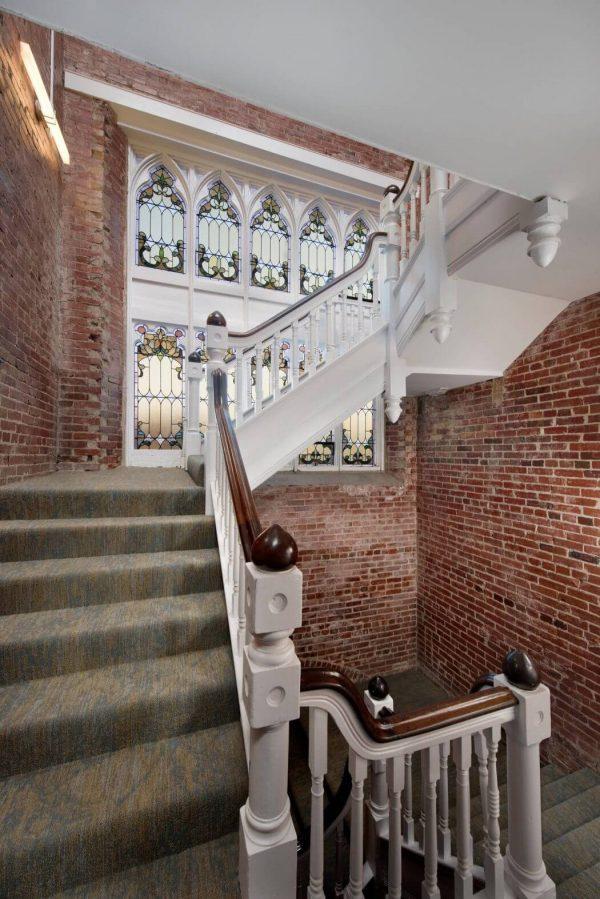 joli escalier dans eglise transformee en maison brique rouge