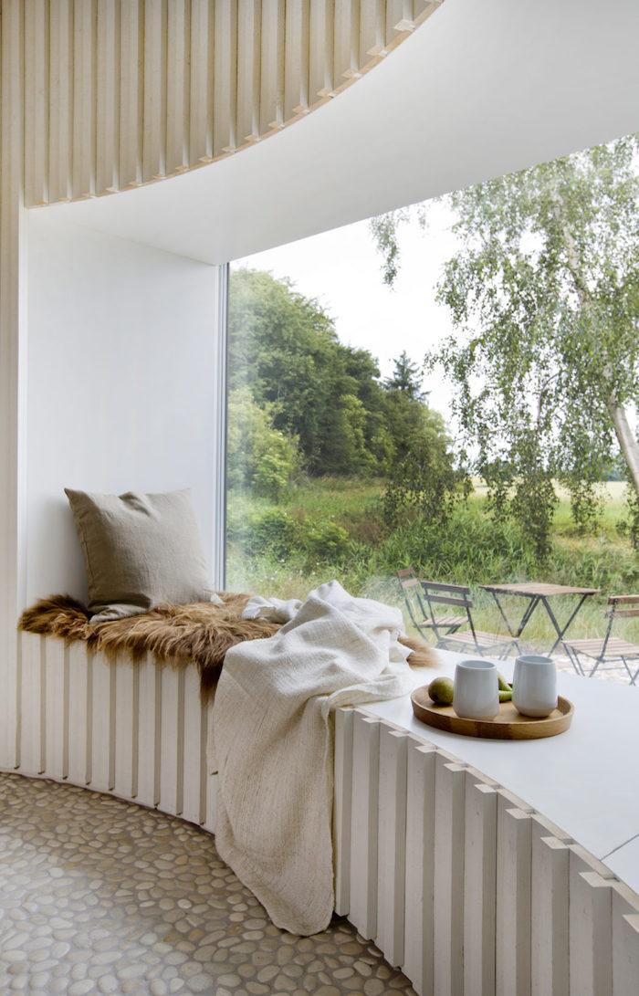 maison cylindrique canape terasse coussins vitre verdure foret fourrure