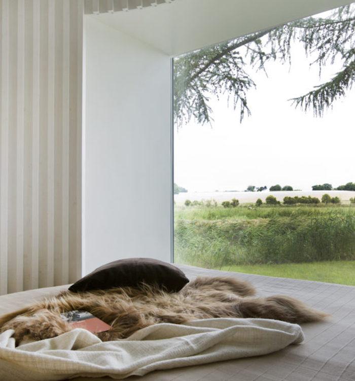 maison ronde chambre fenetre lit vue sur foret matela fourrure coussins blanc bois