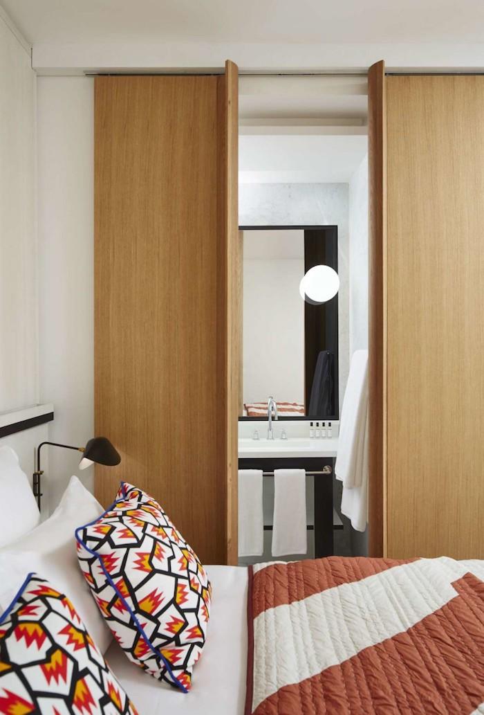 appart parisien toit vue salle de bain blanc et noir linge de lit graphique portes coulissante en bois petite salle d'eau prive