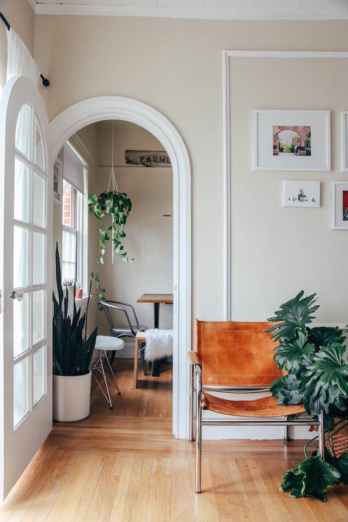 maison californienne fauteuil cuir plantes parquet mur blanc