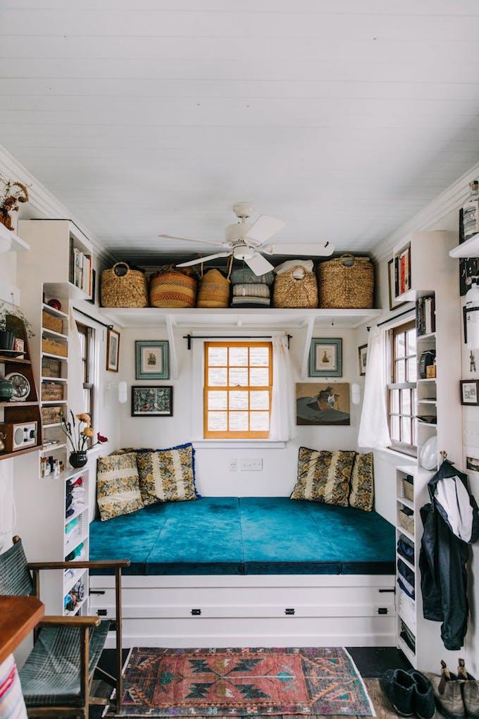 petite maison simple canapé salon séjour petit espace bleu canard cosy bohème coussins paniers osier