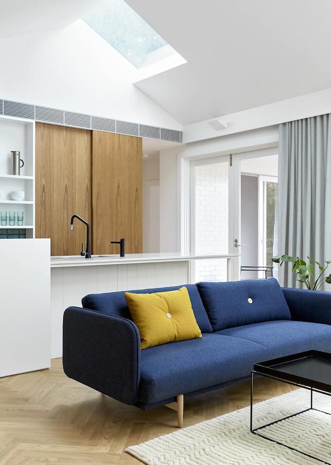 maison avec puits de lumière canapé bleu coussin jaune salon parquet tapis porte coulissante blog déco clem around the corner