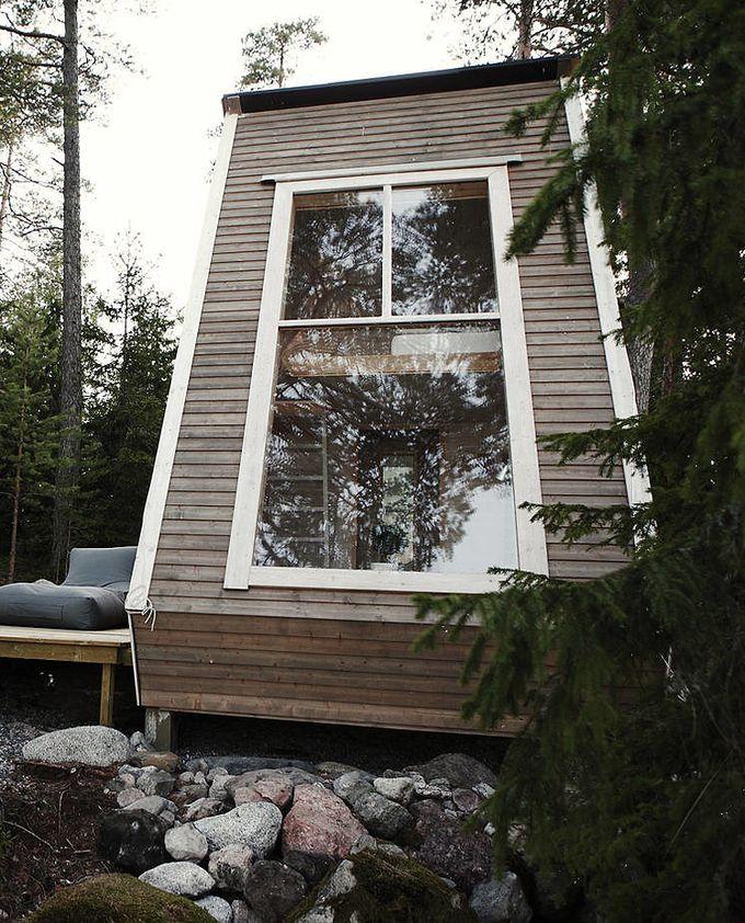 cabane dans les bois chambre salon échelle vitre reflet terrasse fauteuil