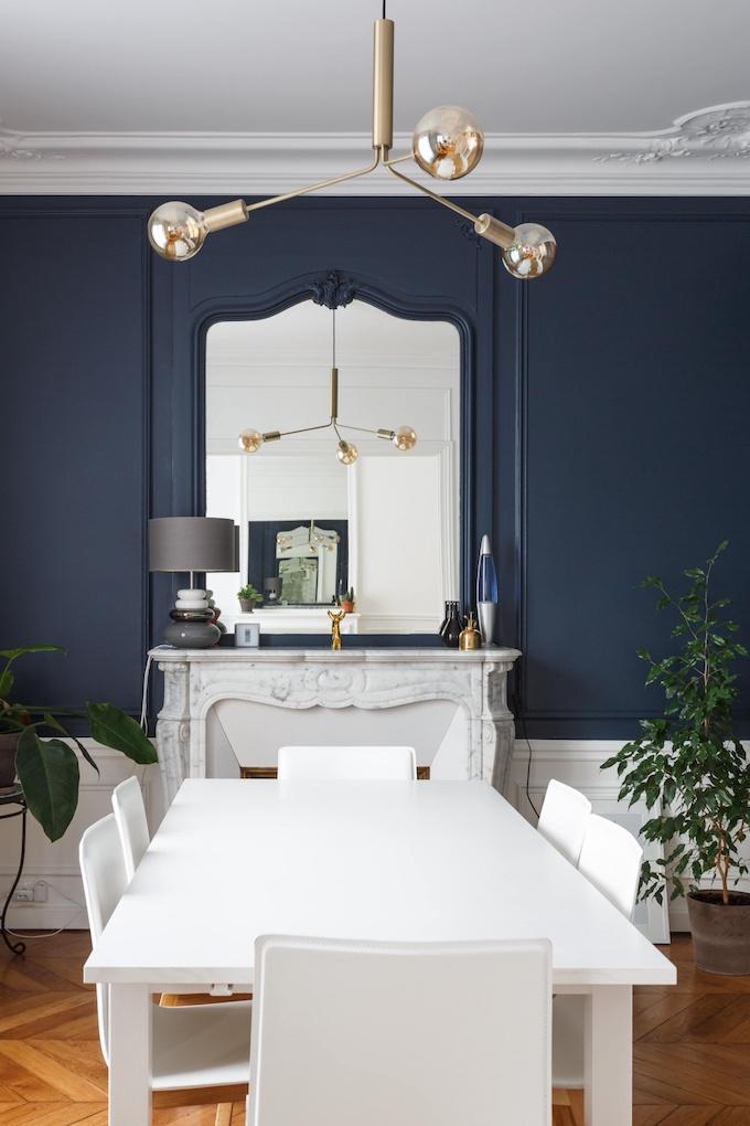 appartement chic parisien salle à manger soubassement blanc moulure suspension abat-jour verre rond mur bleu table parquet bois - blog déco - clemaroundthecorner