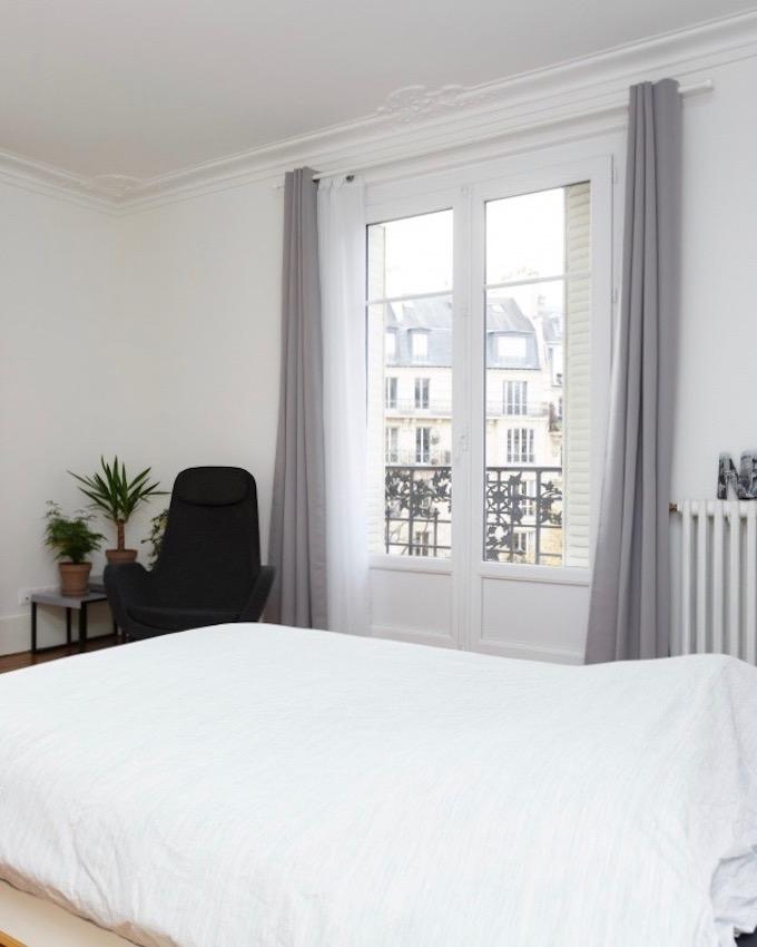 appartement chic parisien chambre lit draps blancs fauteuil noir rideaux gris plante verte petit balcon - blog déco - clemaroundthecorner