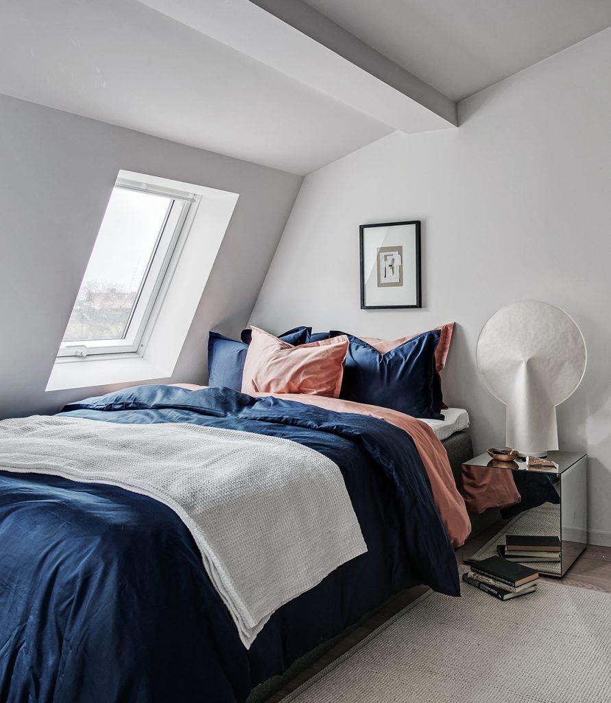 idée déco studio chambre lit bleu marine coussin rose saumon orange tapis beige toit blanc parquet blond - blog déco - clem around the corner
