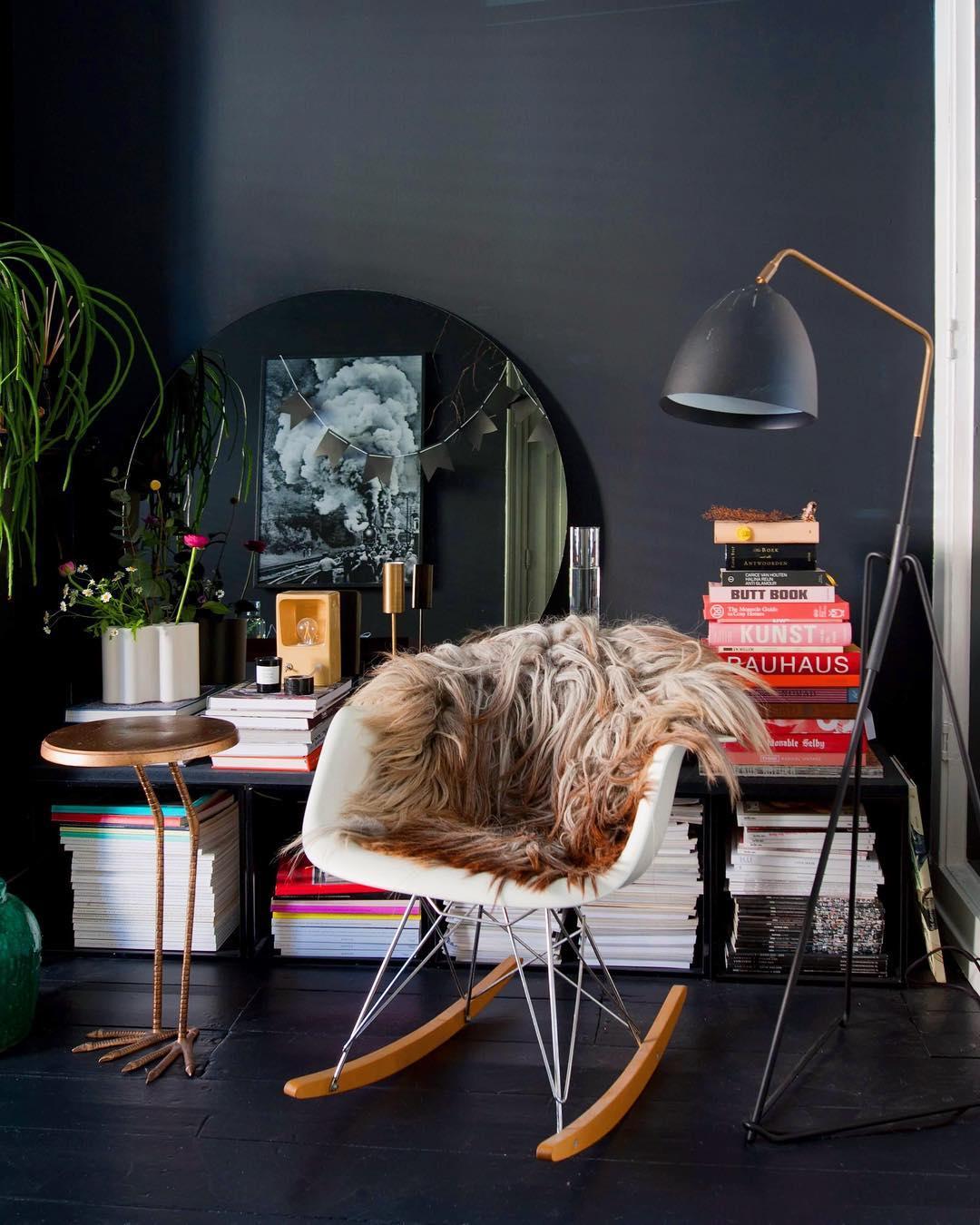 salon noir miroir rond chaise à bascule table basse pied oiseau autruche en cuivre