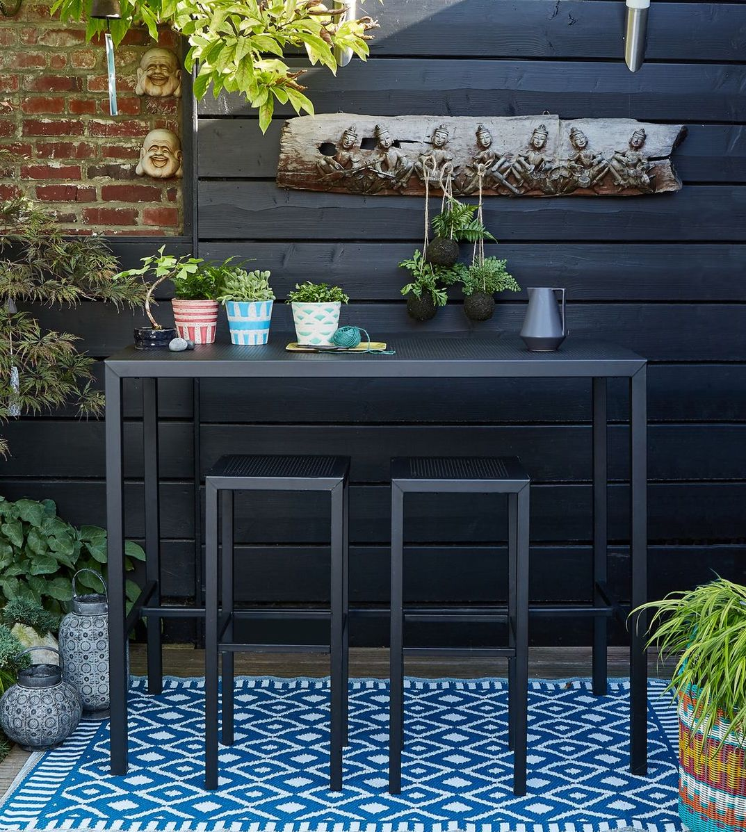 table haute métal noir perforé mur en bois et brique rouge clemaroundthecorner