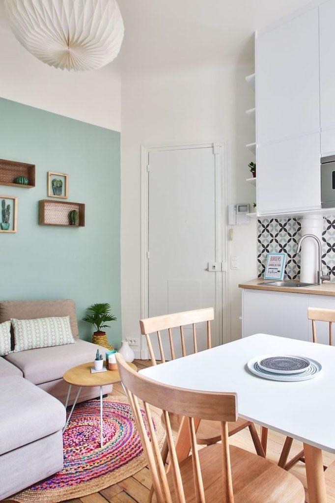 Studio 18m2 paris cuisine ouverte carreaux de ciment suspension papier salon séjour ouvert table chaise bois salle à manger tapis rotin canapé gris
