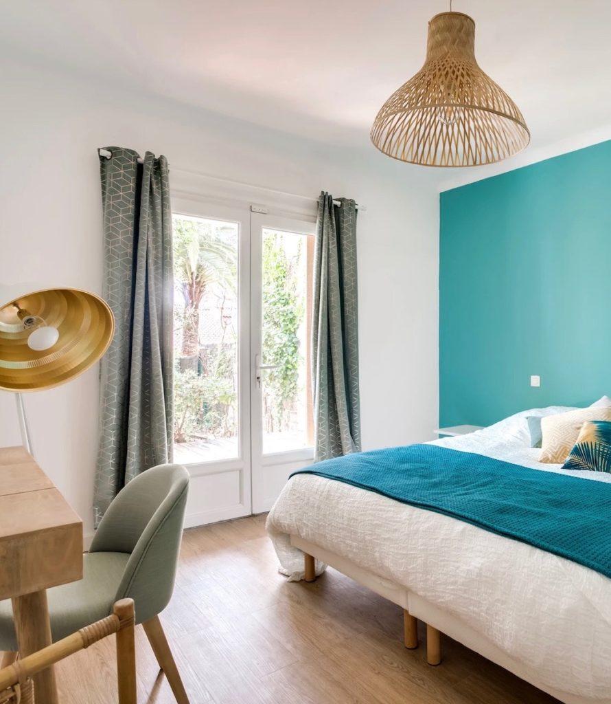 chambre spacieuse mur bleu baie vitrée vue sur jardin suspension luminaire rotin parquet bois - blog déco - clemaroundthecorner