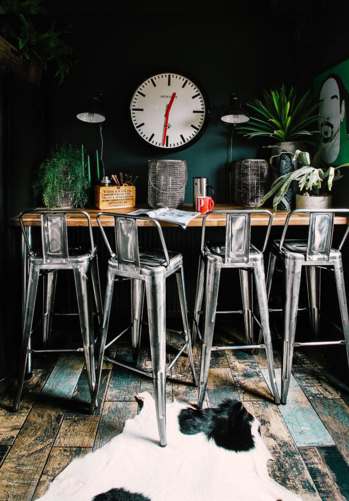 appartement noir salon salle à manger table haute style bar avec chaises industrielles parquet bois foncé