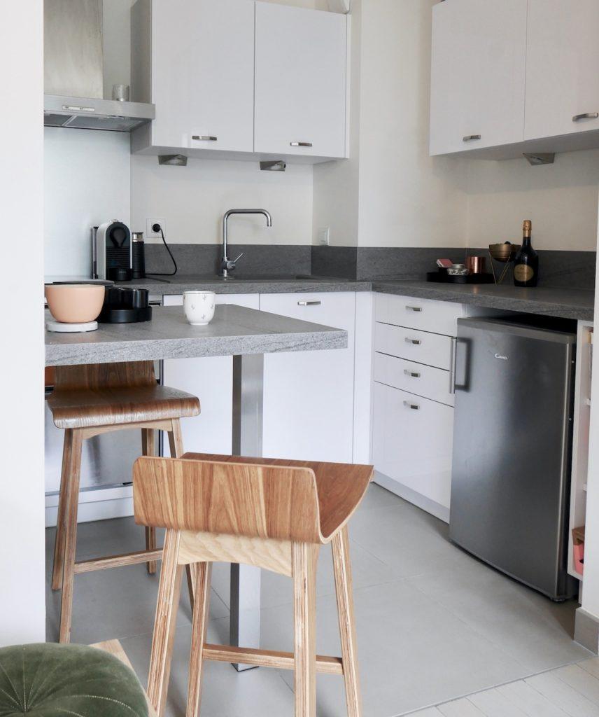 studio bien agencé kitchennette coin cuisine blanche plan de travail béton ciré
