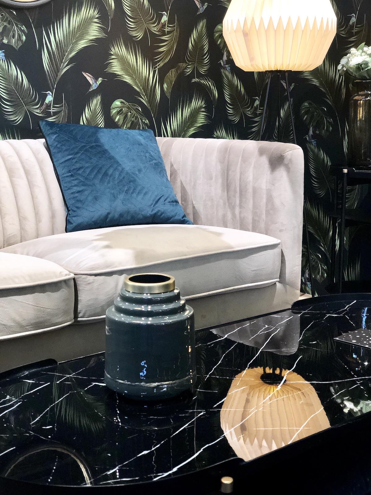 salon foncé mur papier peint noir jungle feuille table marbre ovale noir canapé velours gris années 60 70