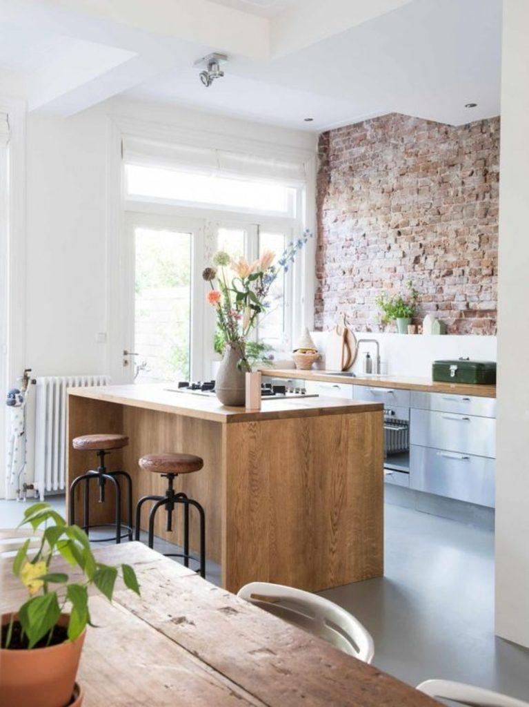 cuisine en bois nature mur en pierre rouge tabouret coussin en cuir marron