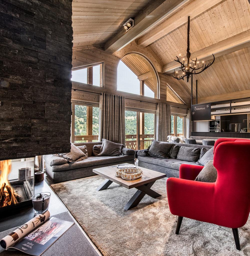 salon moderne chaleureux sophistique cheminée pierres fauteuil rouge clemaroundthecorner