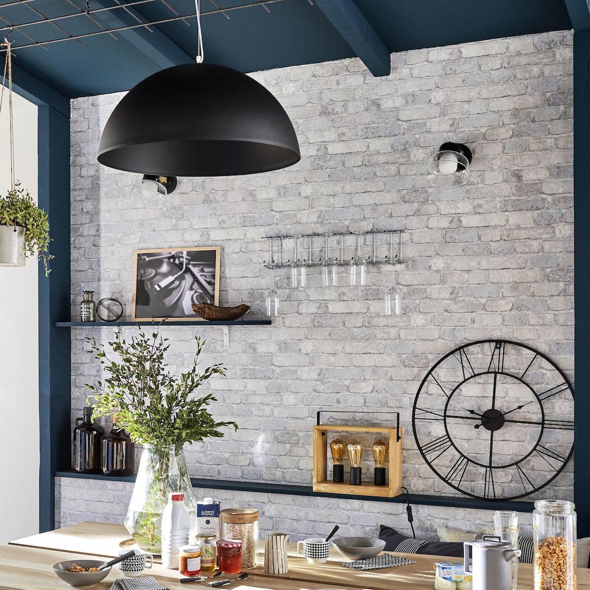 cuisine lumineuse style maison de campagne mur en brique gris peinture bleu marine horloge métallique noire
