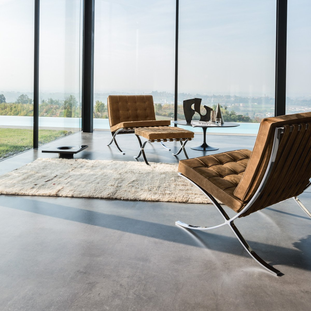 fauteuil barcelona design daim marron tapis moumoute table tulipe noir - blog déco - clematc