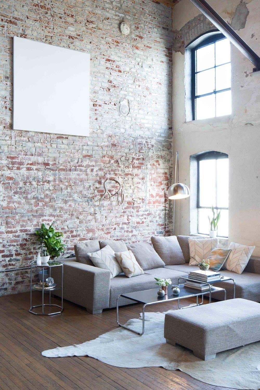 salon industriel mur en briques sol parquet en bois lamé canapé d'angle gris
