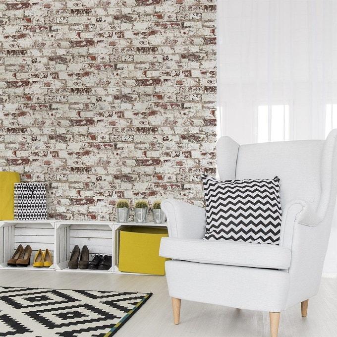 salon scandinave industriel mur briques rouges effacées fauteuil gris clair tapis coussin noir et blanc géométrique
