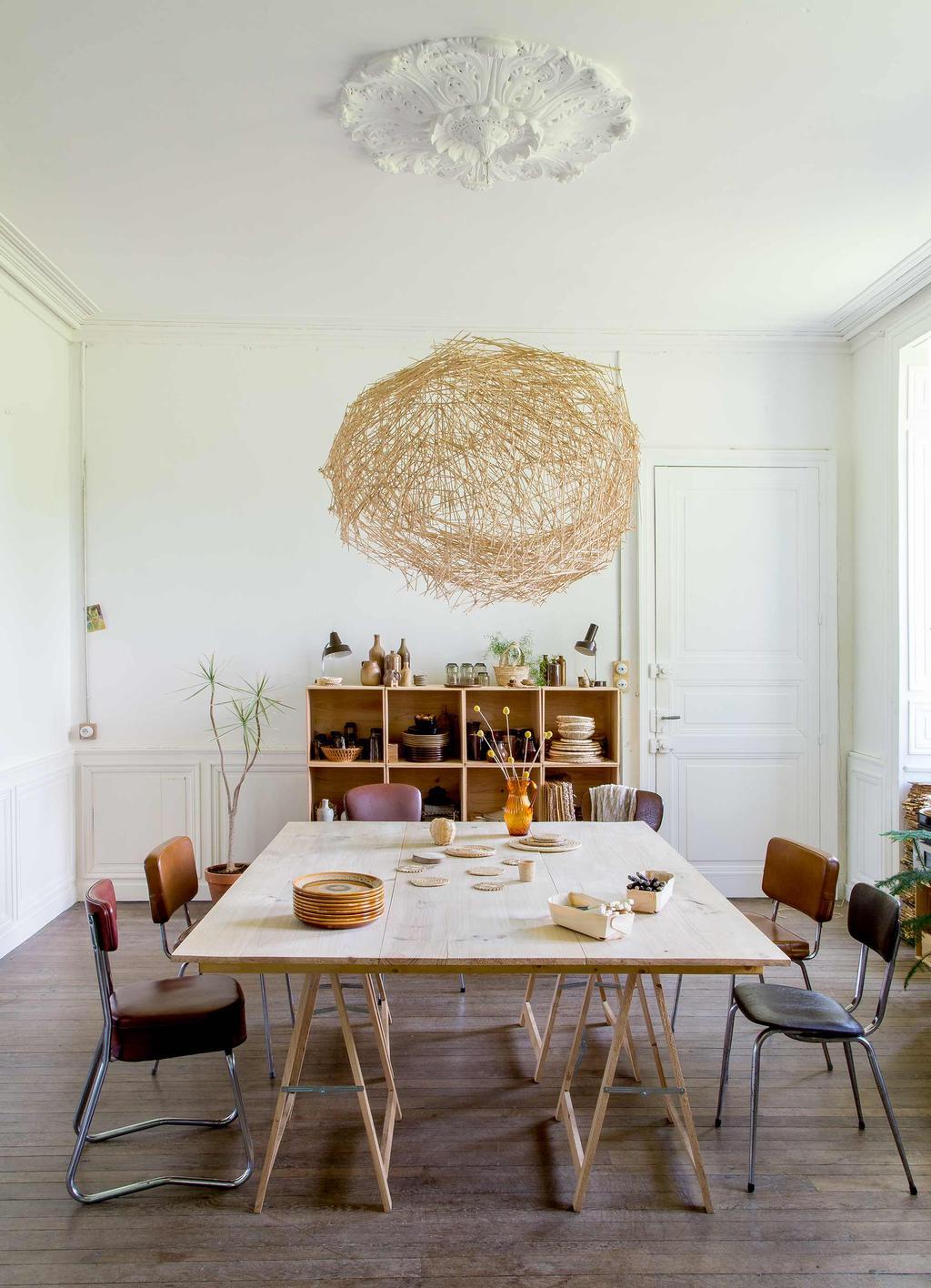salle à manger table bois avec tréteaux chaises vintage en cuir suspension fibres naturelle moulures au mur