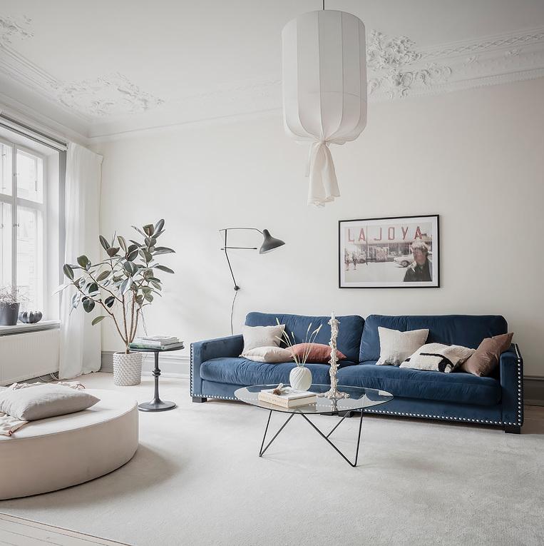 salon spacieux tapis extra large canapé bleu marine velours table basse verre pied métallique noire pièce lumineuse blanche