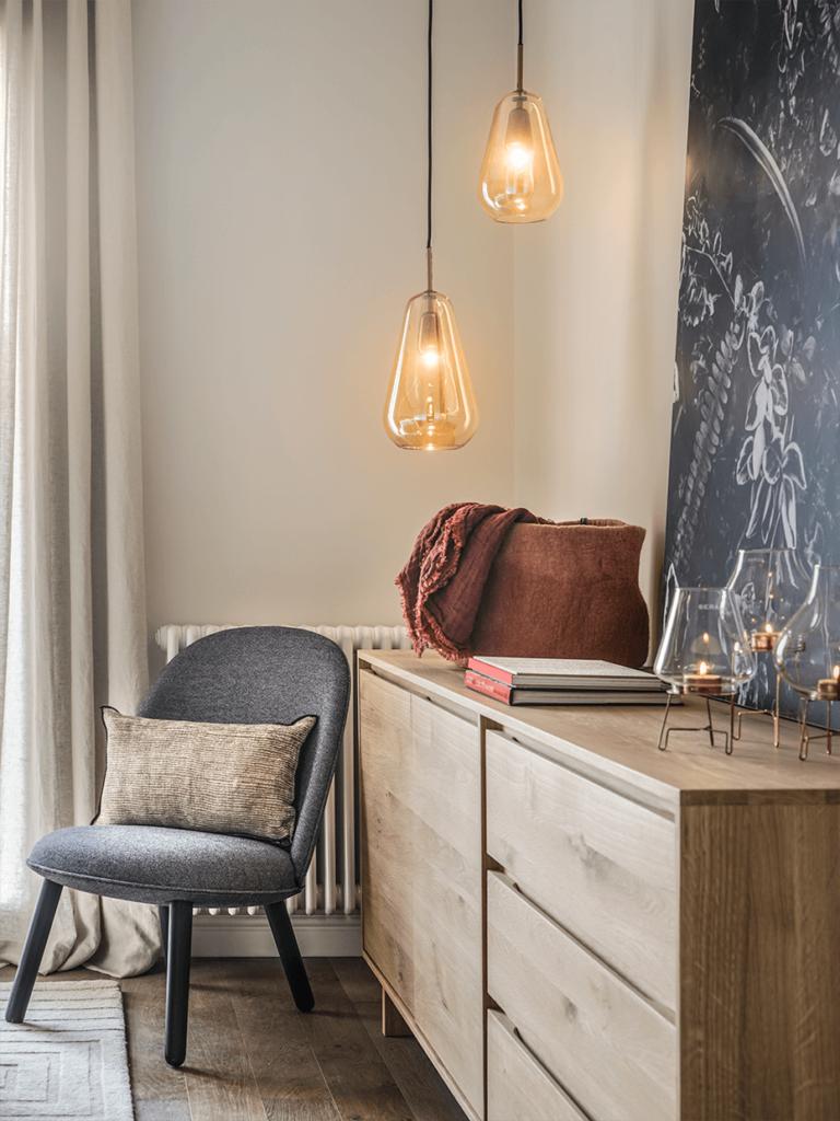 appartement Eixample chambre parentale fauteuil gris buffet bois élégant sobre