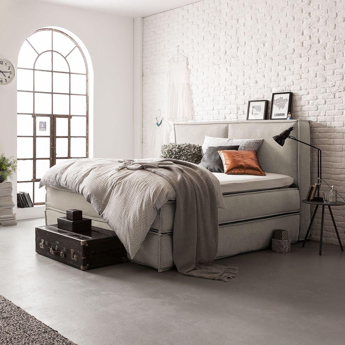 lit boxspring beige suite parentale mur en briques blanches fenêtre métallique noir