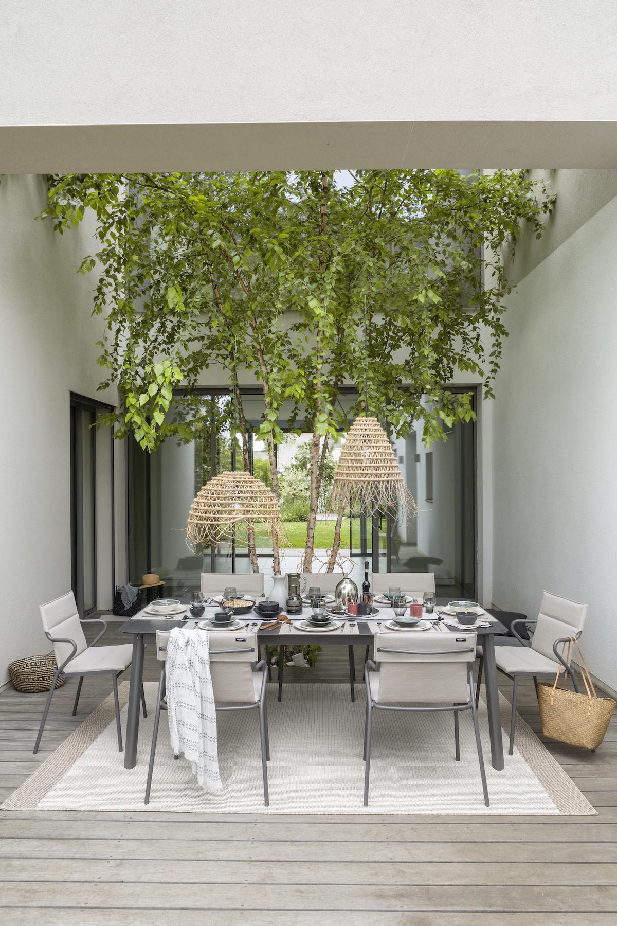 patio cour intérieure maison table extérieur grise chaise fauteuil beige empilable