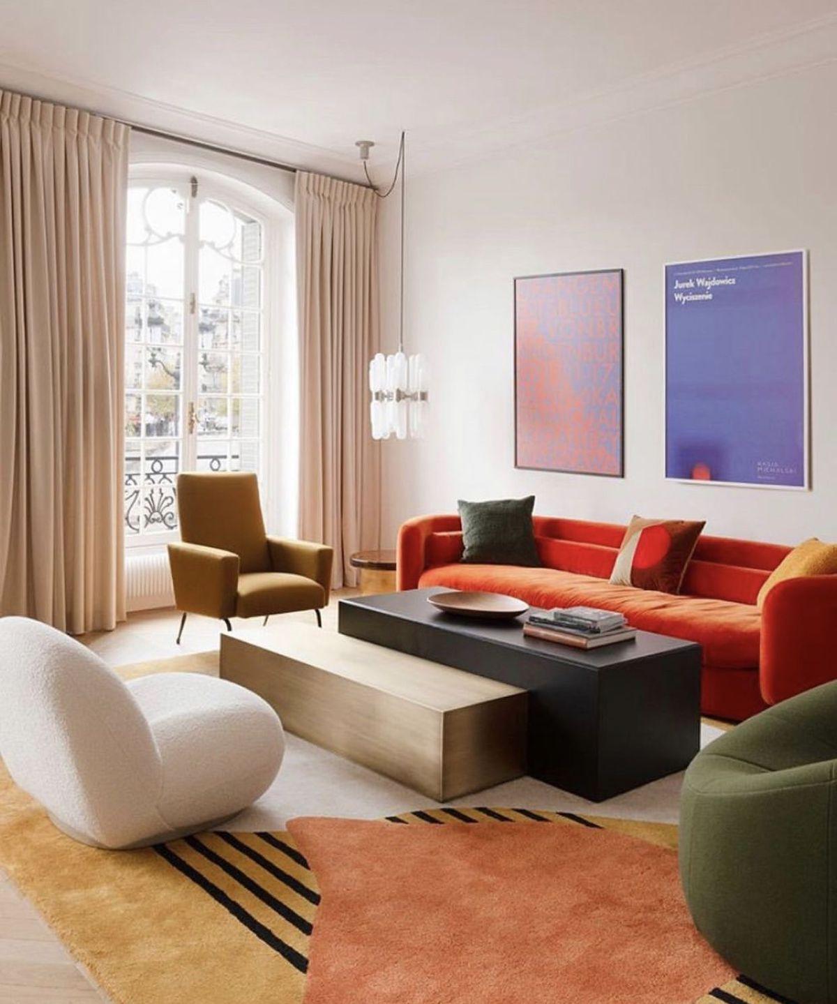 salon coloré rétro canapé orange fauteuil vert blanc tapis motifs géométrique table salon rectangulaire