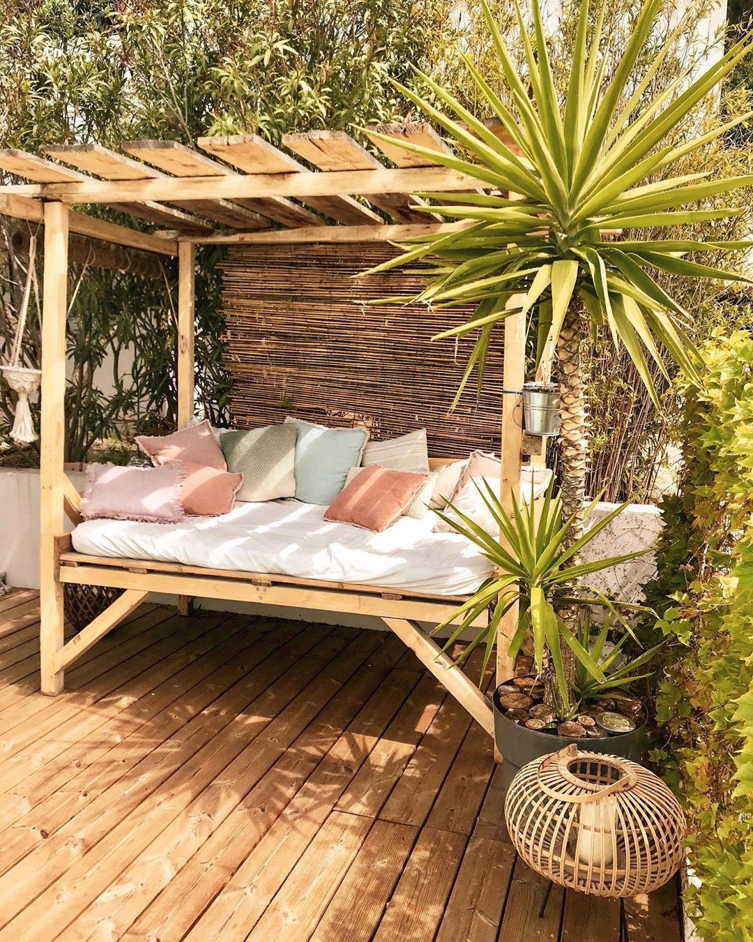 salon de jardin banquette en bois coussins rose bleu vert pastel palmier lanterne bois