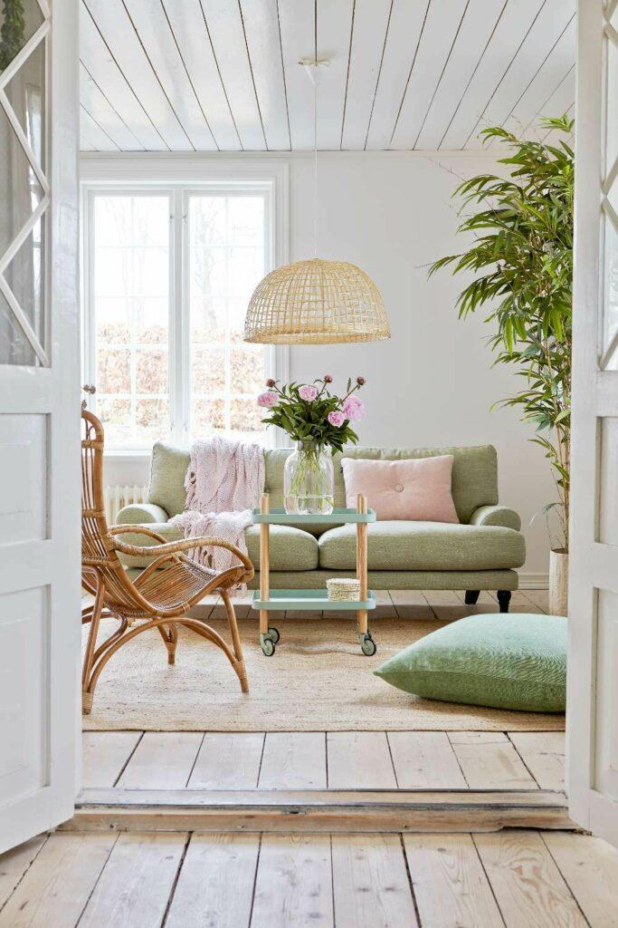 séjour lumineux canapé vert menthe coussin rose pastel fauteuil osier déco douce vintage