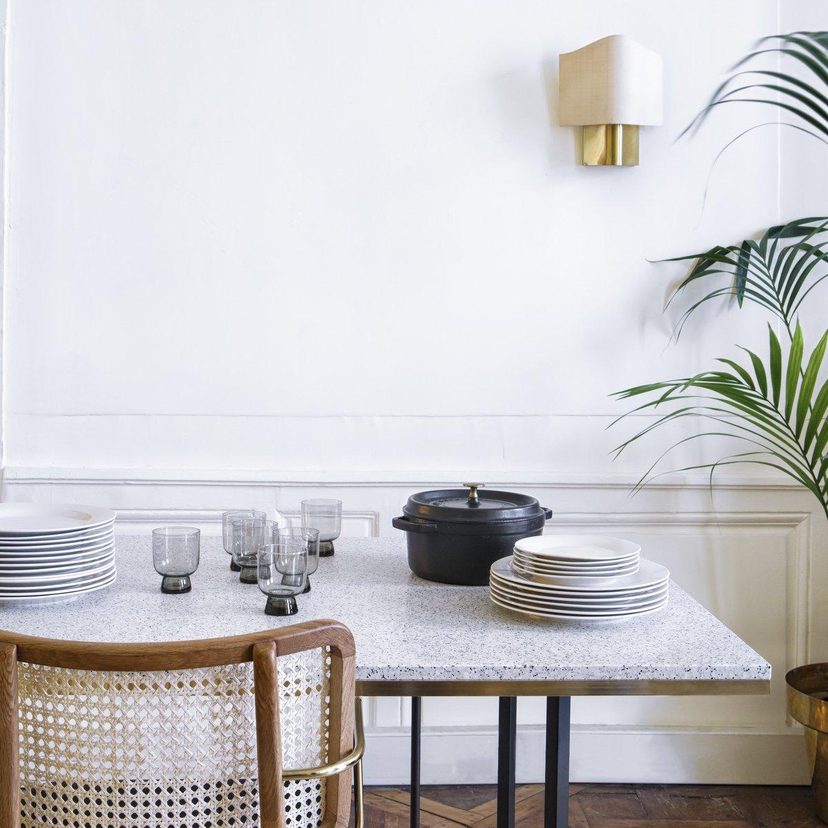 salle à manger table terrazzo petit carreaux noir et blanc chaise cannage bois mur moulure blanc