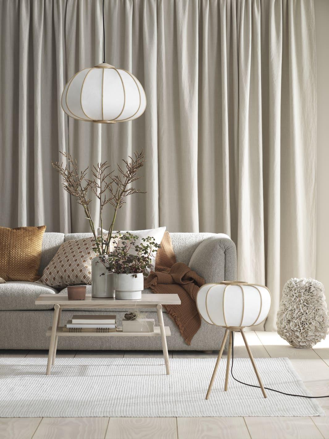 salon élégant canapé gris lampe laiton coussin orange table basse bois