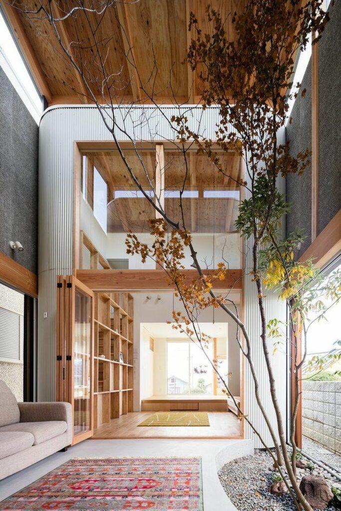 salon en longueur lumineux étagère bois arbre incrusté grande fenêtre