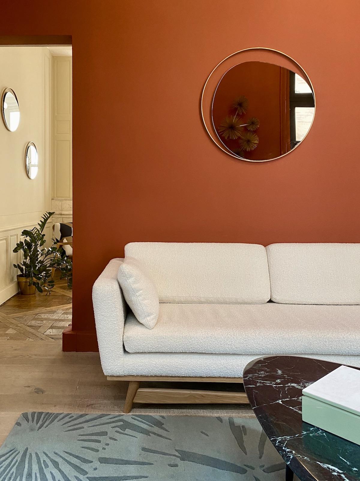 salon canapé bouclette gris clair mur orange terracotta peinture table basse marbre ovale