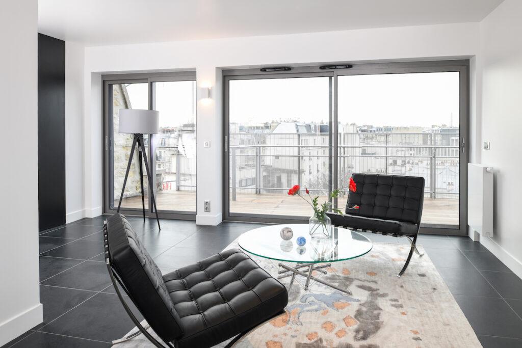 salon moderne blanc noir carrelage fauteuil Barcelona chauffeuse cuir
