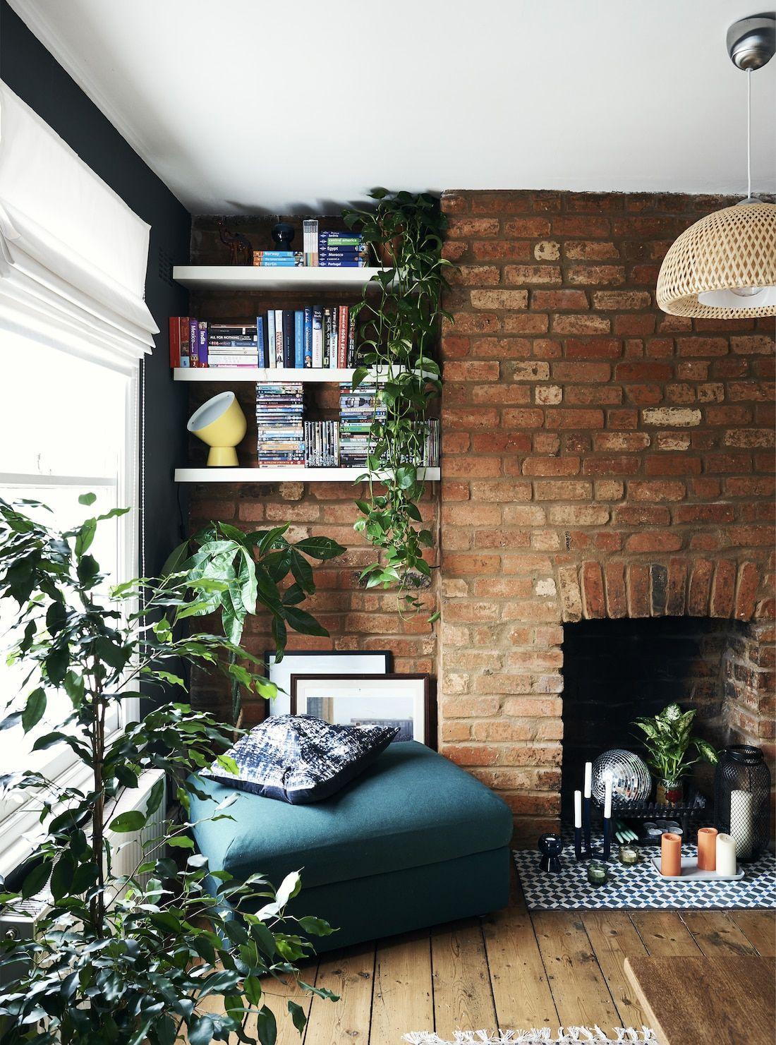 Salon cosy rustique mur en brique rouge fauteuil bleu canard plantes vertes