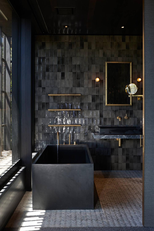 salle de bain chic total look noir baignoire rectangle béton miroir lampe laiton
