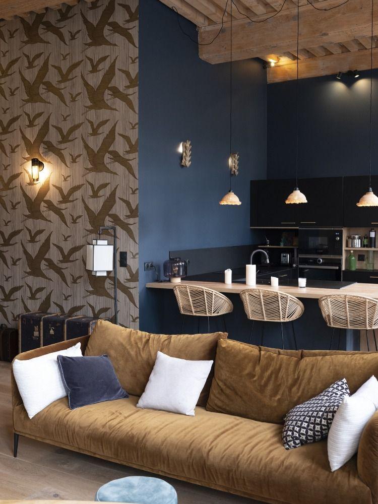 salon cuisine ouverte canapé velours jaune taupe chaise haute rotin mur bleu