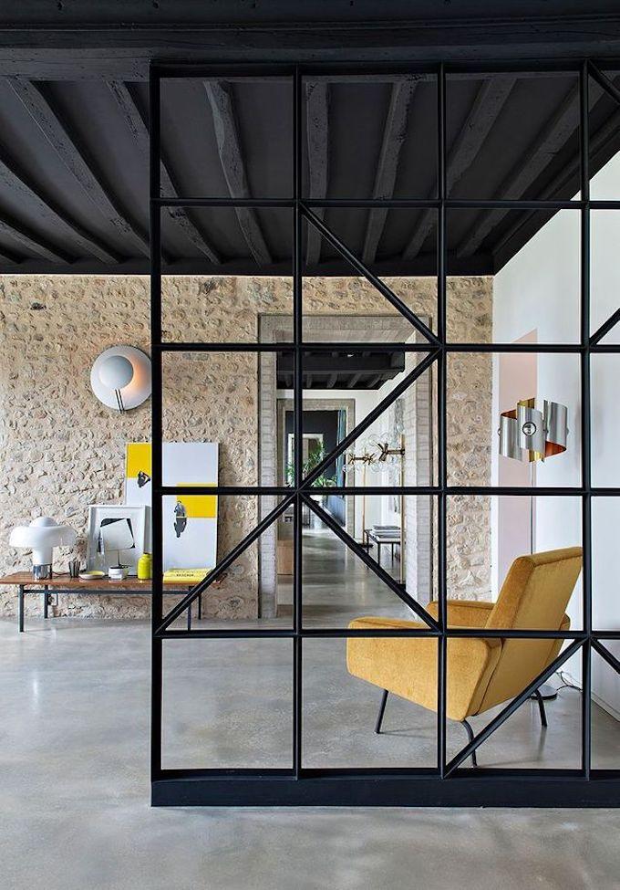 salon estival jaune mur en brique marron verrière métallique noir