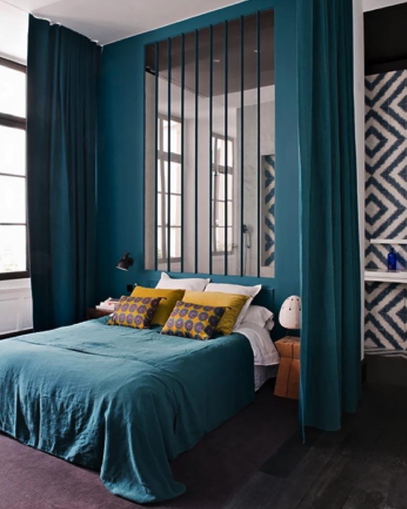 chambre parentale lit double bleu canard coussins jaunes papiers peints géométriques