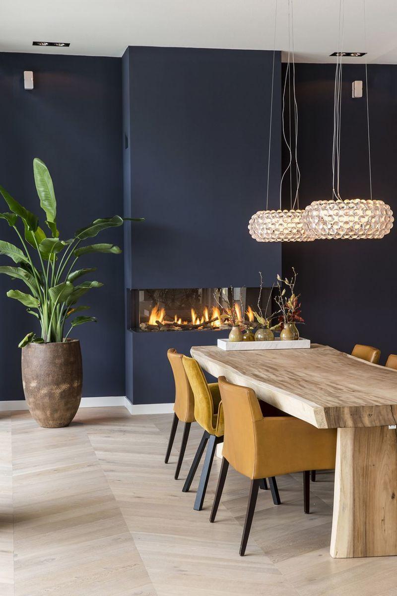 salle à manger table bois brut chaises jaunes moutarde mur bleu marine parquet bois lamé