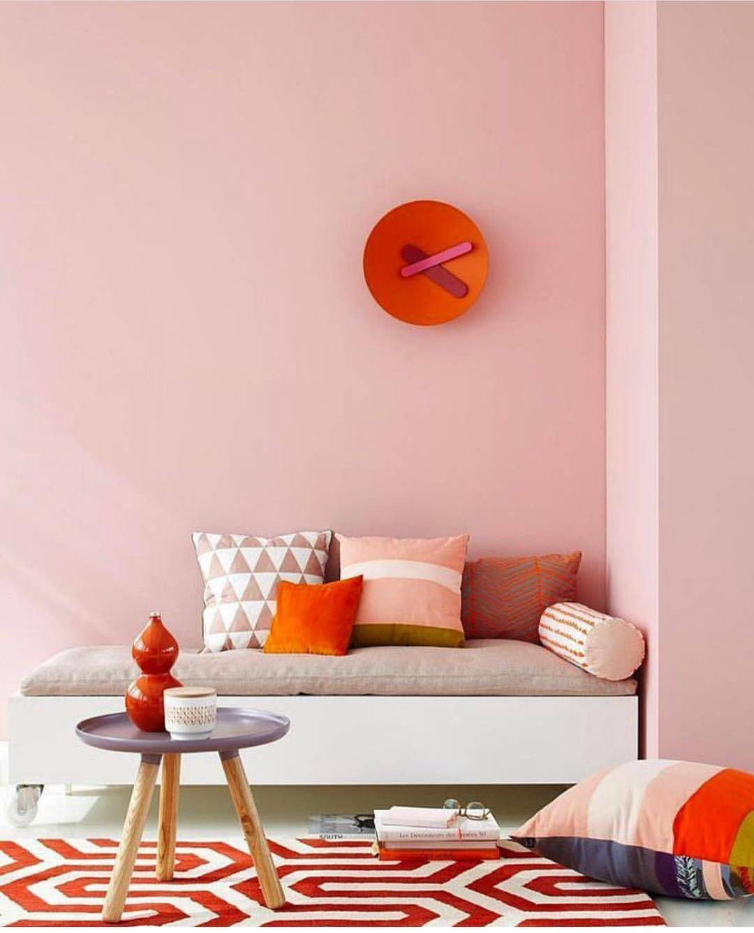 salon coin lecture printanier mur rose pastel coussins orange
