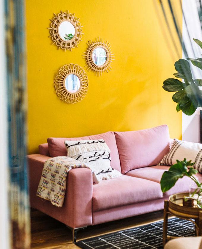 salon estival mur jaune canapé rose pastel coussin frange tapis noir et blanc