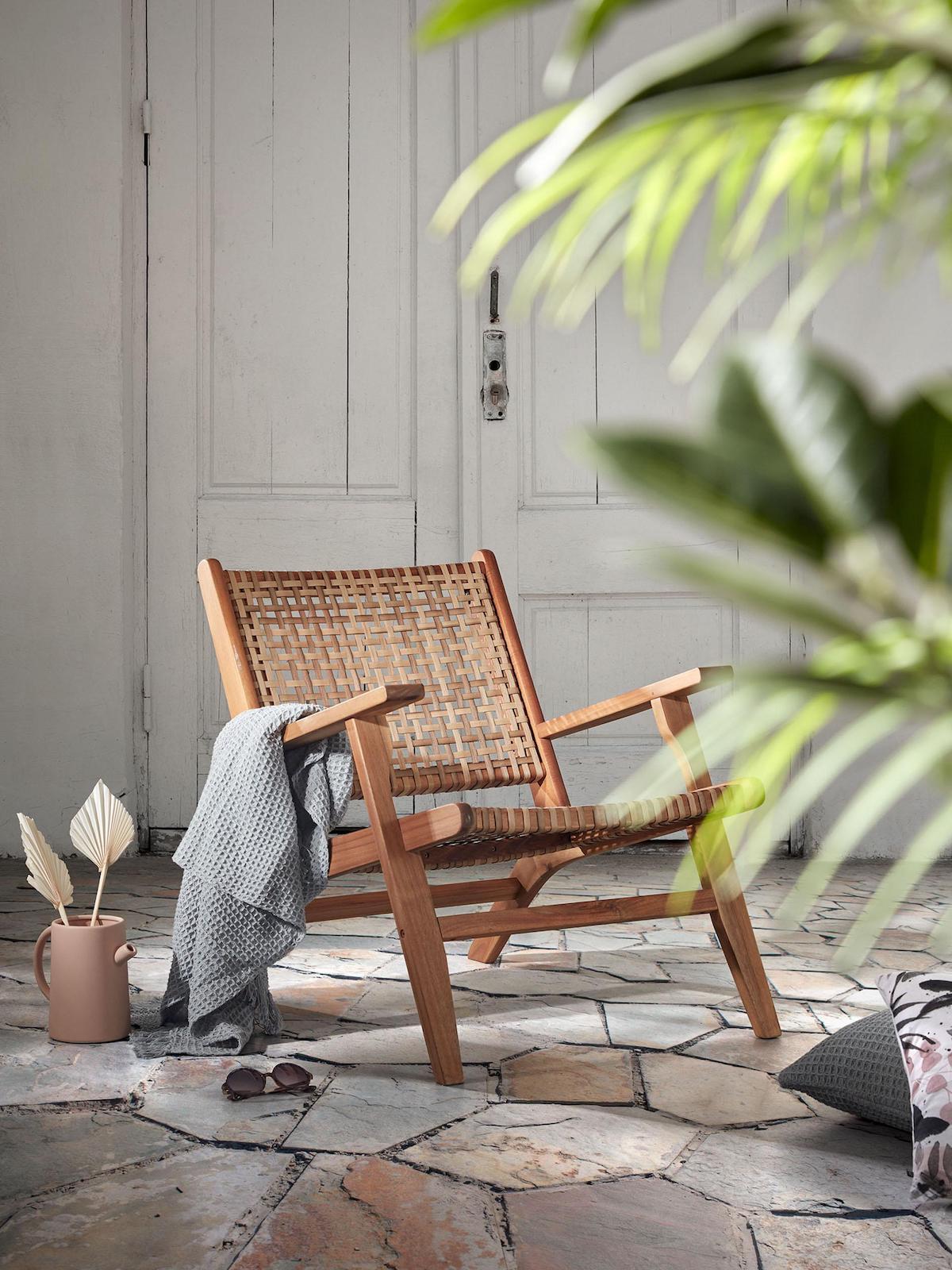 fauteuil cannage bois plante verte plaid gris coussin de sol